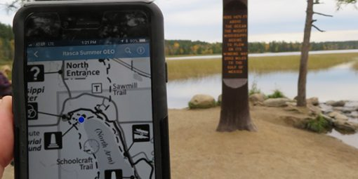 Person holding a GeoPDF showing their location (blue dot) at Itasca headwaters