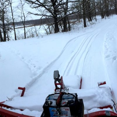 A view from the snowmobile of a freshly groomed ski trail