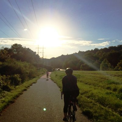 A biker heads towards the setting sun