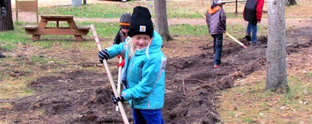 A young girl rakes the soil