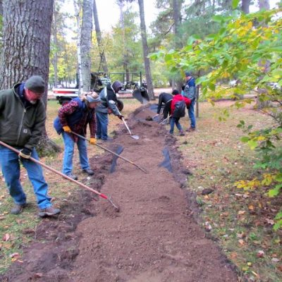 volunteers prepare the soil for installing the nature playground