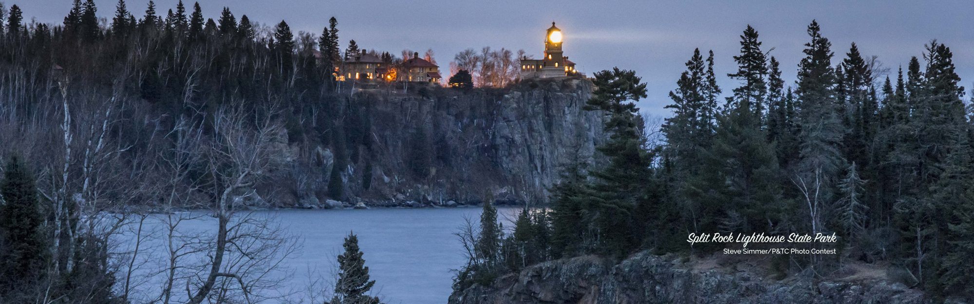 Split Rock Lighthouse shining light over snowy landscape