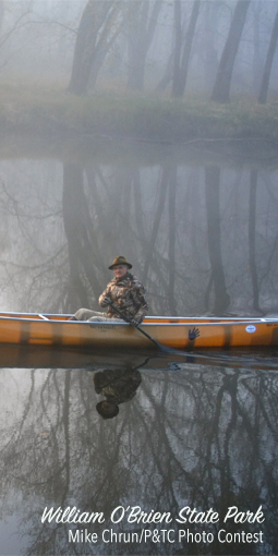 Man canoeing through misty river