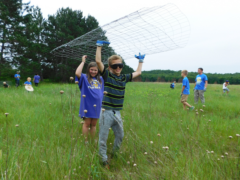 two kids carry the tree cage across the prairie