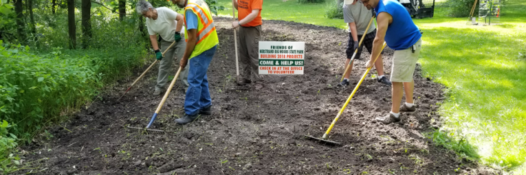 friends with rakes prepare the soil