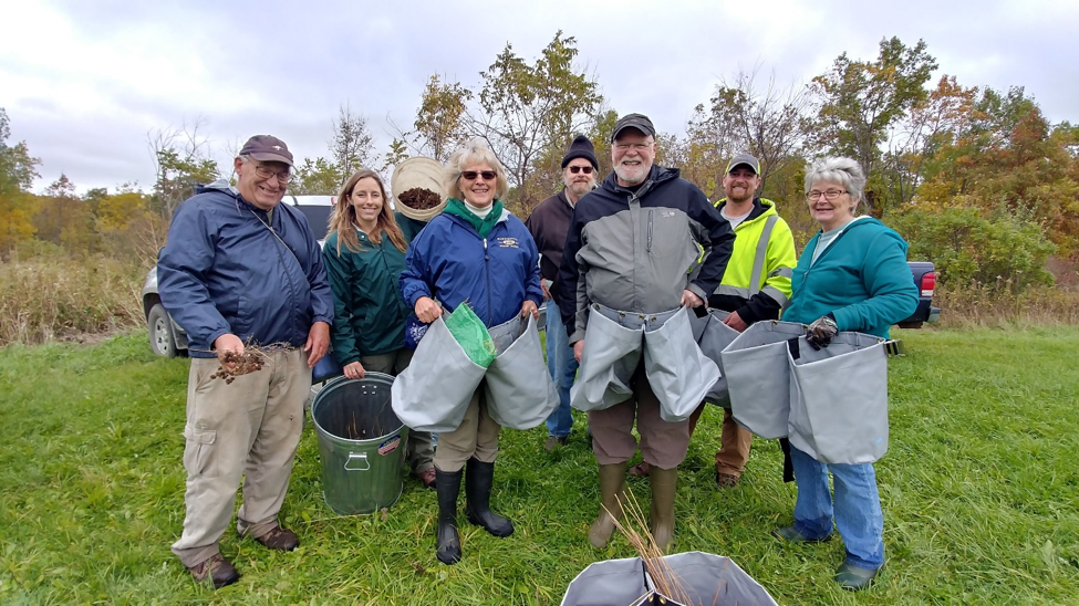 a group poses with their newly picked prairie seeds