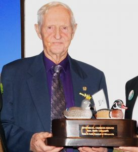 Older man holding award