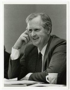 Sen. Langseth smiling and sitting at table with his face resting on his hand
