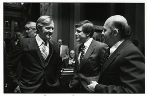 Black and white photo of three men in suits talking.
