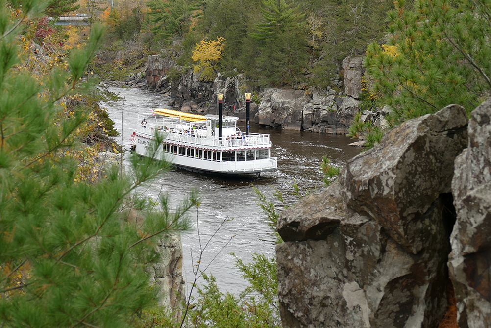 paddleboat on St. Croix River with rocks in foreground