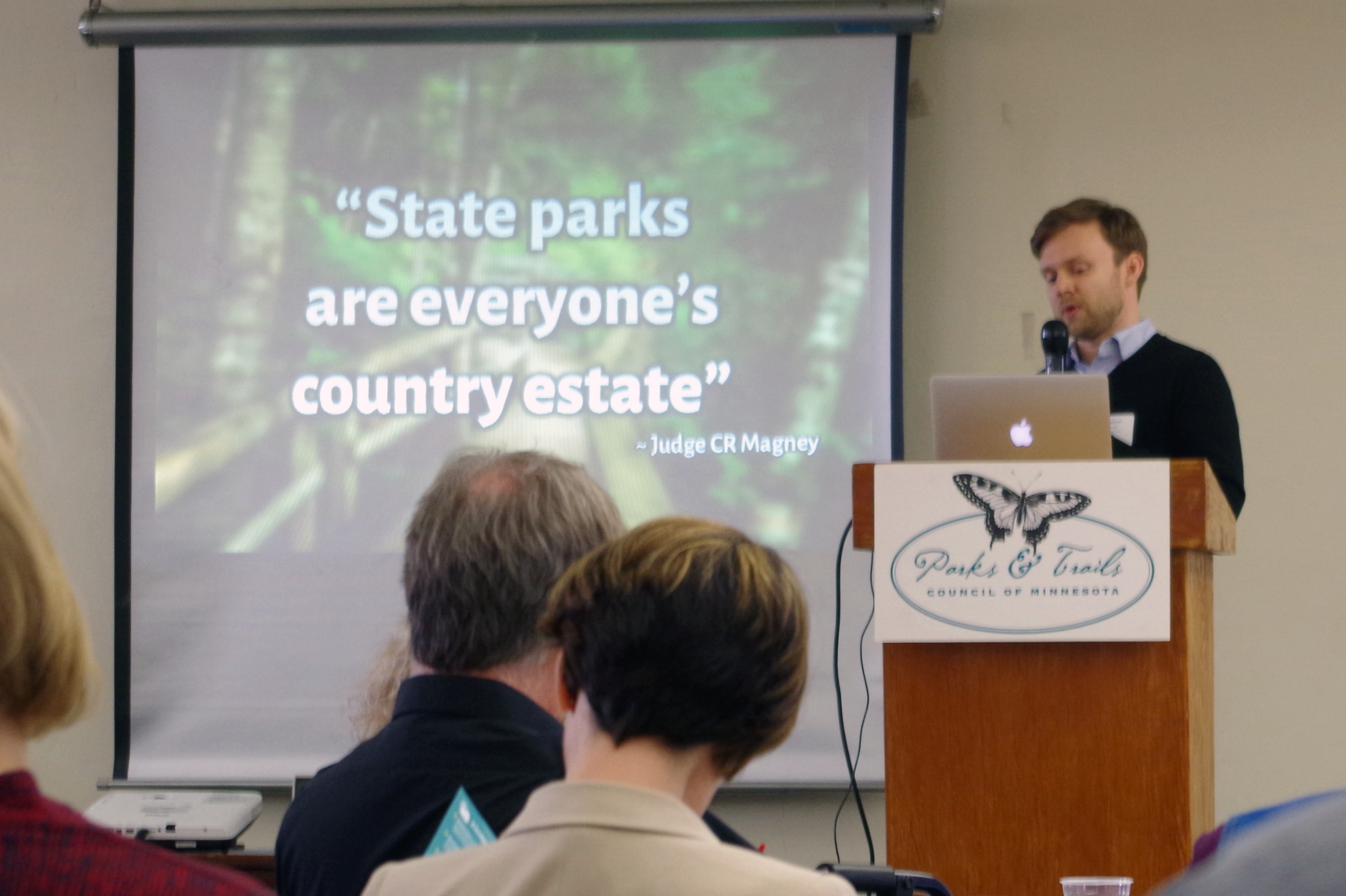 "Man at podium with slide behind saying ""State Parks are everyone's country estate"""