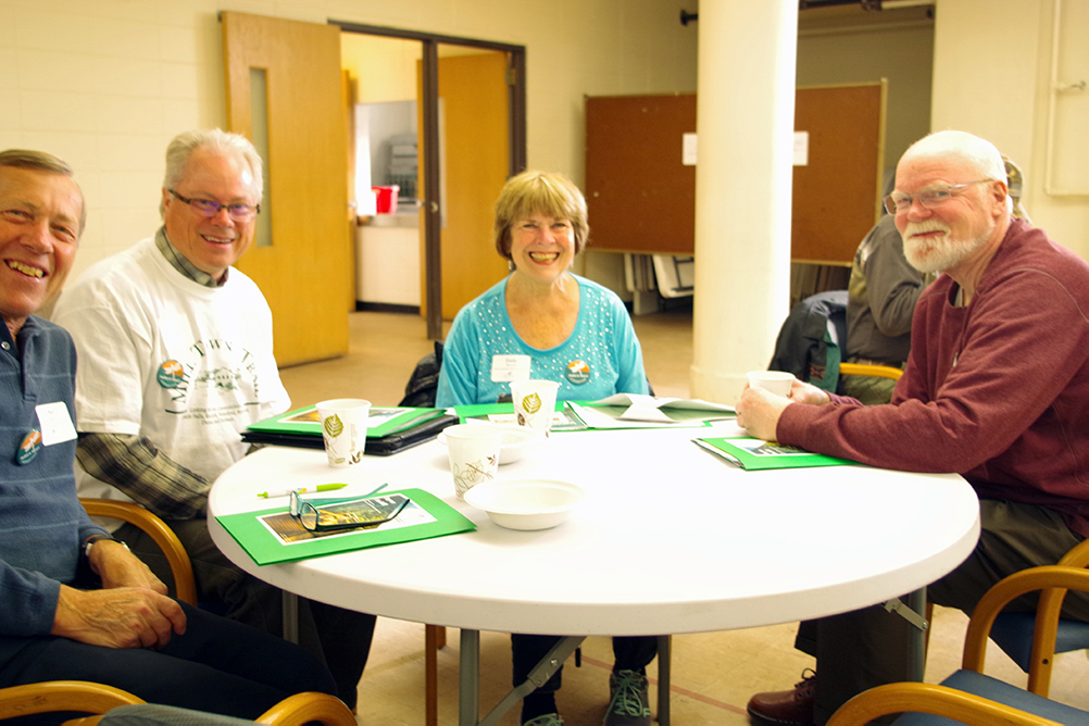 three men and woman sitting at a table smiling.