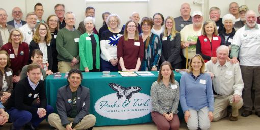 Group of 50+ people grouped around table with Park & Trails Council logo