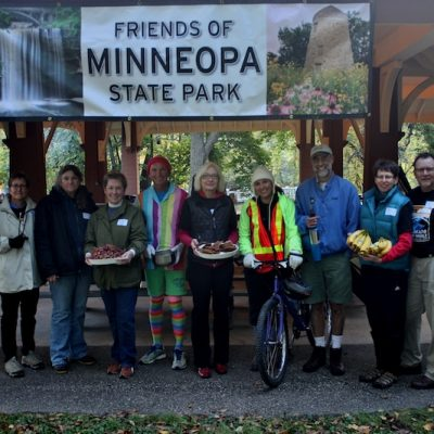 Friends pose with their food and a bike in front of the picnic shelter