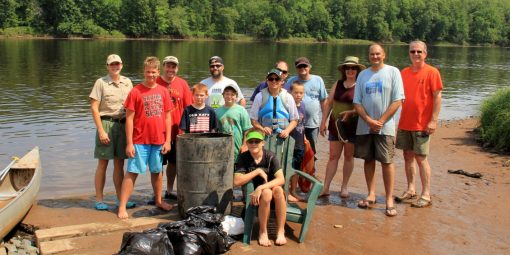 Volunteers stand by the water with the trash they collected during the clean up