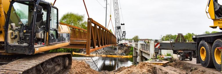 crane installing a trail bridge over a river