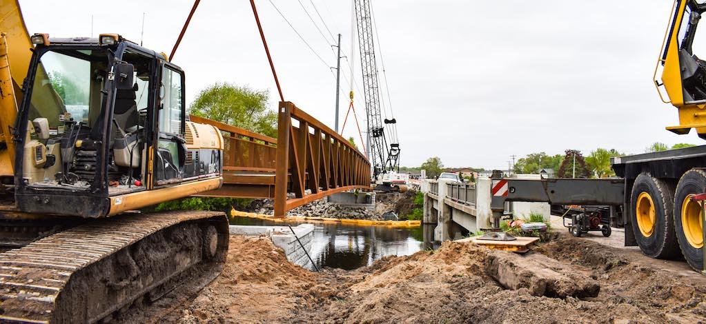 crane installing a trail bridge over a river