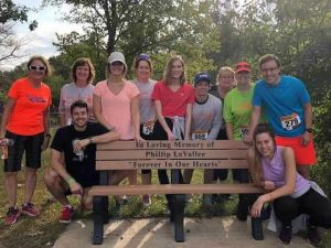 Runners posing with a memorial bench