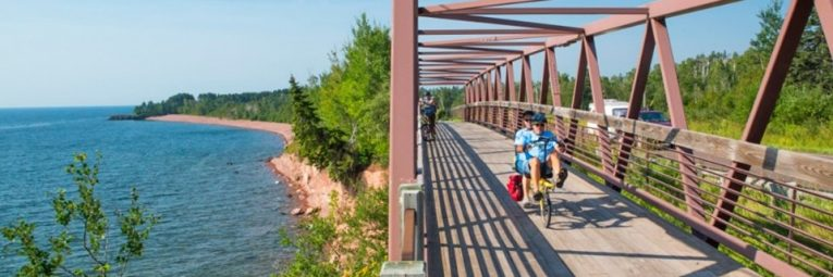 Bike ride info over picture of tandem riders coming over a bridge