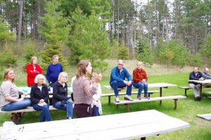 workshop attendees listen to a discussion on picnic tables outside