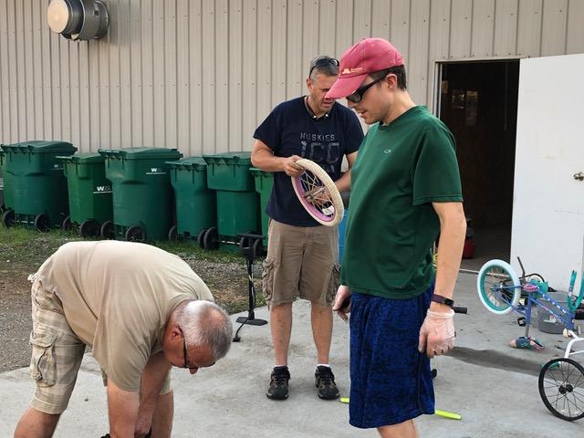 three men repair bike parts