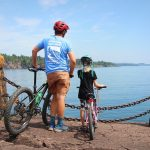Father and daughter look over lake Superior with bikes