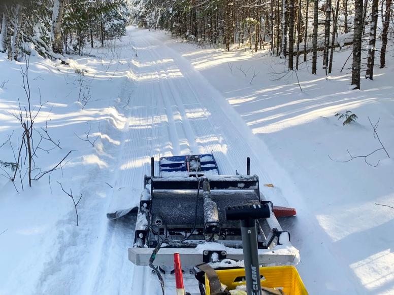 Trail groomer moving along ski trail