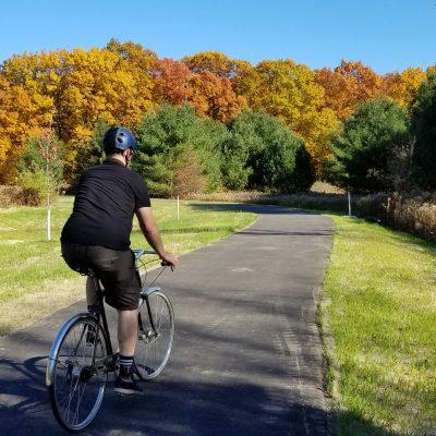 man bicycling on fresh pavement