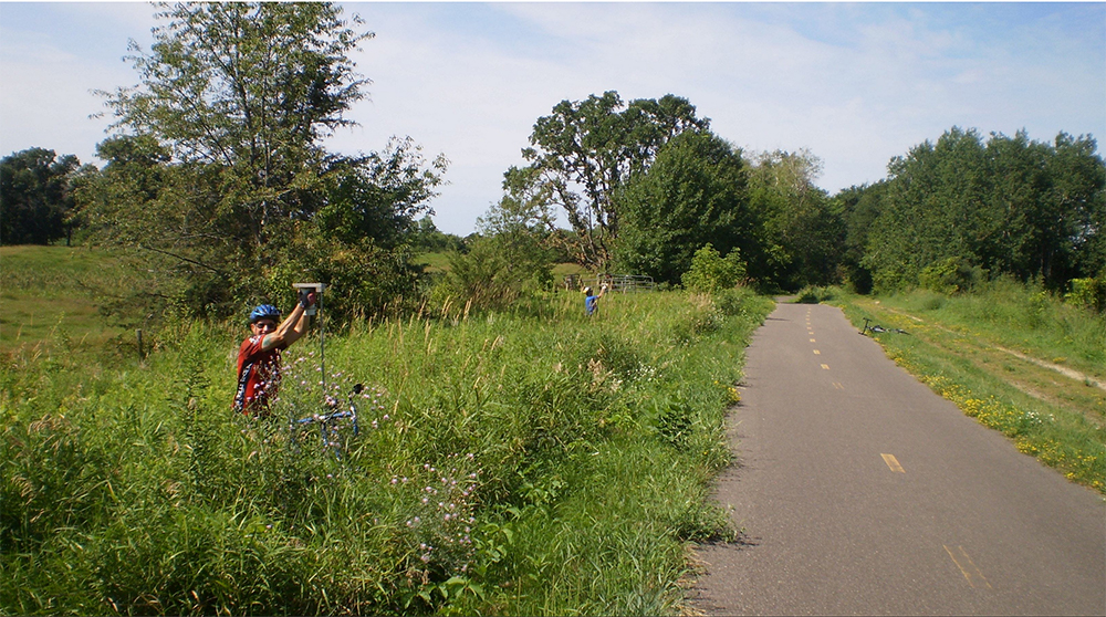 Man in biking outfit stands in tall grass