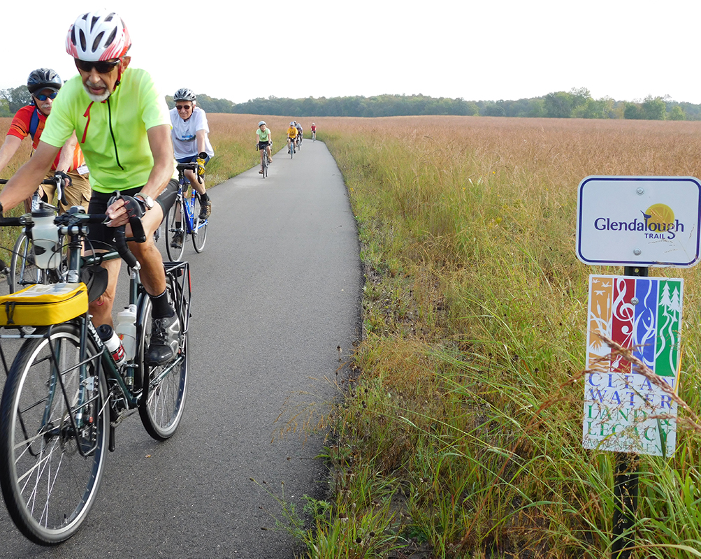 Bicyclists on paved trail with sign