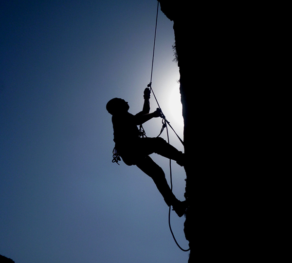 silhouette of person climbing on cliff