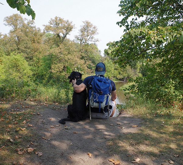 Person sitting on ground with dog