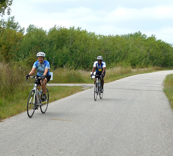 two people bicycling on paved trail