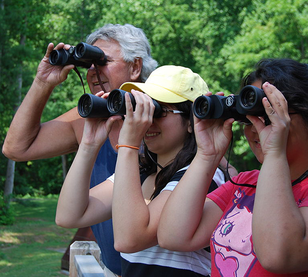 three people with binoculars