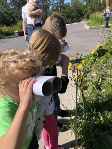 kids look through cardboard roll binoculars