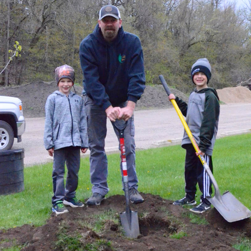 dad and two kids shoveling a hole to plant a tree