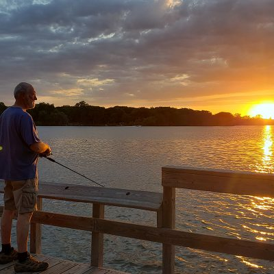 Older man fishing on pier at sunset