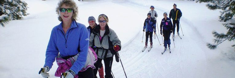 Group of Nordic skiers going up a small hill