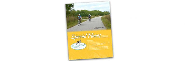 cover of newsletter shows two bicyclists
