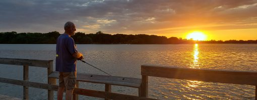 Man fishing on dock with sunrise peeking over lake