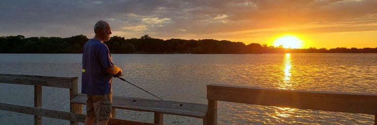 Man fishing on dock with sunrise peeking over lake
