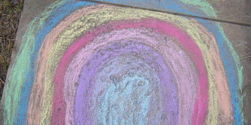 a rainbow in chalk on a sidewalk