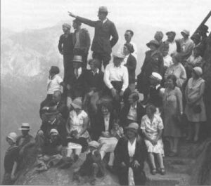 Black and white photo of ranger pointing as group of 30 people look