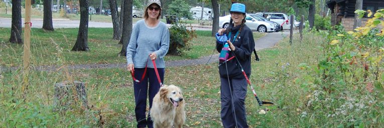 Two hikers leave the trailhead with their dogs