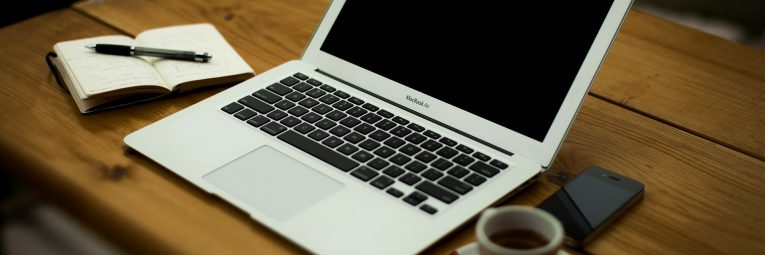Laptop on wooden table with espresso cup and notebook