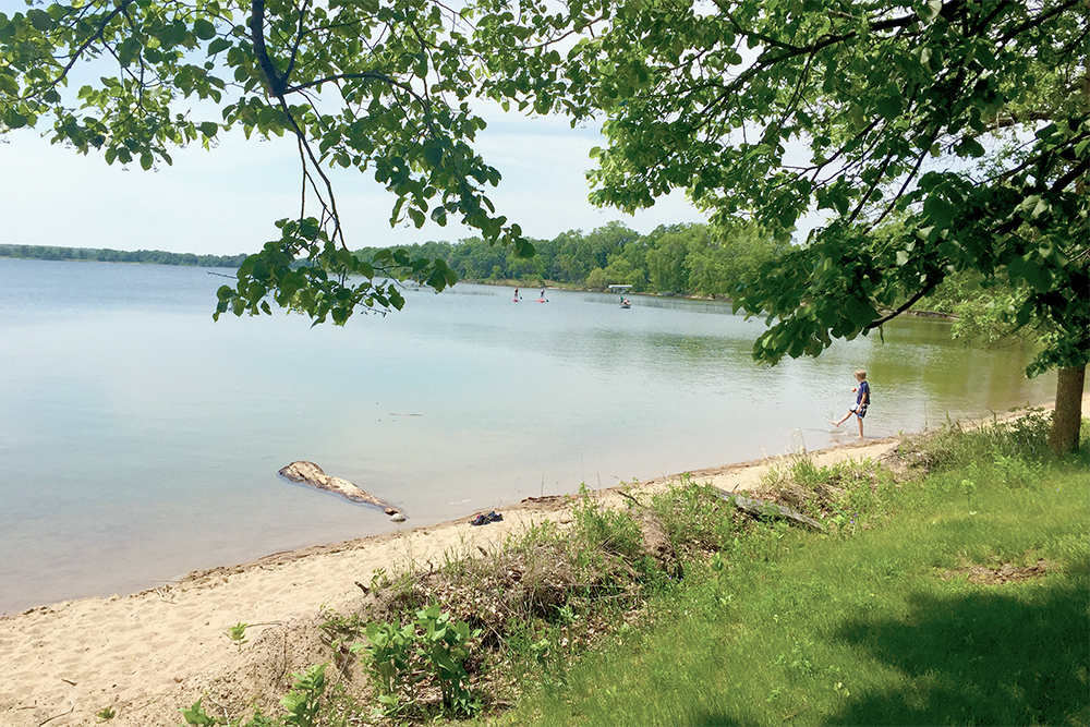 sandy lakeshore with boy wading in water
