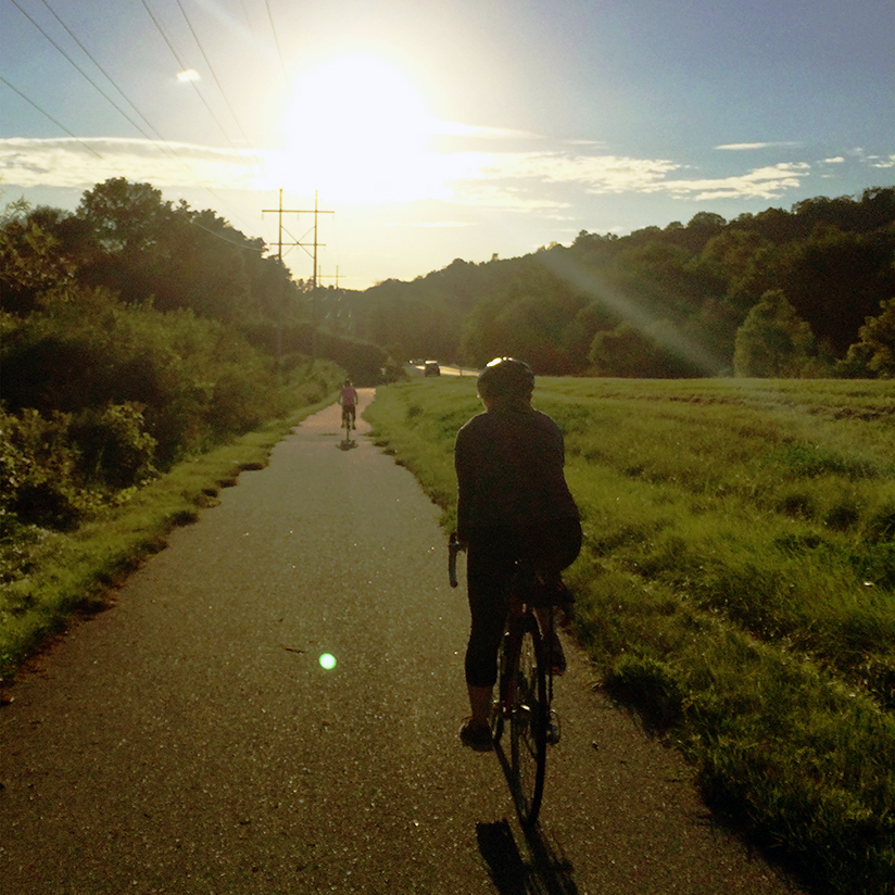 bicyclist on paved path with bright sun