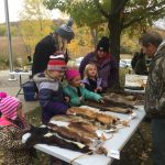 kids learning about animal furs from a volunteer