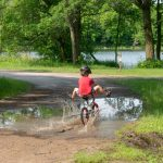 kid riding bike through puddle