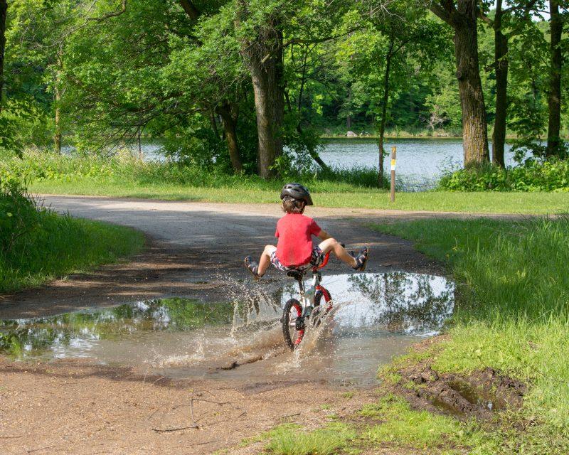 kid riding bike through puddle